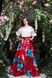 Ελκυστική γυναίκα στην κόκκινη φούστα στο floral κήπο Αφηρημένες ανασκοπήσεις φαντασίας με το μαγικό βιβλίο Στοκ φωτογραφία με δικαίωμα ελεύθερης χρήσης