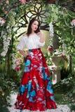 Ελκυστική γυναίκα στην κόκκινη φούστα στο floral κήπο Αφηρημένες ανασκοπήσεις φαντασίας με το μαγικό βιβλίο Στοκ Φωτογραφίες