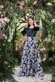 Ελκυστική γυναίκα στη φούστα στο floral κήπο Αφηρημένες ανασκοπήσεις φαντασίας με το μαγικό βιβλίο Στοκ φωτογραφία με δικαίωμα ελεύθερης χρήσης