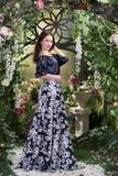 Ελκυστική γυναίκα στη φούστα στο floral κήπο Αφηρημένες ανασκοπήσεις φαντασίας με το μαγικό βιβλίο Στοκ Φωτογραφία