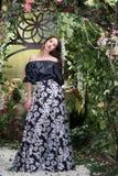 Ελκυστική γυναίκα στη φούστα στο floral κήπο Αφηρημένες ανασκοπήσεις φαντασίας με το μαγικό βιβλίο Στοκ Φωτογραφίες