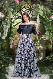 Ελκυστική γυναίκα στη φούστα στο floral κήπο Αφηρημένες ανασκοπήσεις φαντασίας με το μαγικό βιβλίο Στοκ εικόνα με δικαίωμα ελεύθερης χρήσης
