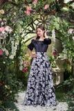 Ελκυστική γυναίκα στη φούστα στο floral κήπο Αφηρημένες ανασκοπήσεις φαντασίας με το μαγικό βιβλίο Στοκ Εικόνες
