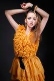 Ελκυστική γυναίκα στο κίτρινο φόρεμα με τα χέρια επάνω από το κεφάλι της Στοκ φωτογραφία με δικαίωμα ελεύθερης χρήσης