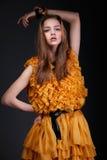 Ελκυστική γυναίκα στο κίτρινο φόρεμα με το χέρι επάνω από το κεφάλι της Στοκ Φωτογραφίες