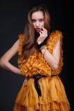 Ελκυστική γυναίκα στο κίτρινο φόρεμα με το χέρι κοντά στο πρόσωπό της Στοκ Φωτογραφία
