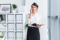 Ελκυστική γυναίκα υπάλληλος που μιλά στο τηλέφωνο, που έχει τις διαπραγματεύσεις, τη χρησιμοποίηση κινητές και την ταμπλέτα στην  στοκ εικόνες με δικαίωμα ελεύθερης χρήσης