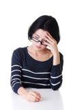 Ελκυστική γυναίκα eyeglasses που κάθεται από τον πίνακα. Στοκ φωτογραφίες με δικαίωμα ελεύθερης χρήσης