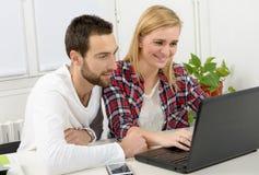 Ελκυστική επιχείρηση ανδρών και γυναικών που χρησιμοποιεί το φορητό προσωπικό υπολογιστή Στοκ Φωτογραφίες