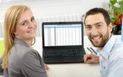 Ελκυστική επιχείρηση ανδρών και γυναικών που χρησιμοποιεί το φορητό προσωπικό υπολογιστή Στοκ Εικόνα