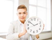Ελκυστική επιχειρηματίας που παρουσιάζει άσπρο ρολόι στοκ εικόνα