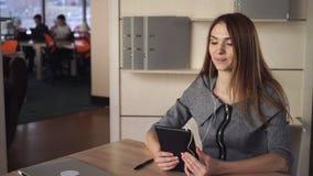 Ελκυστική επιχειρηματίας που χρησιμοποιεί app στην ταμπλέτα οθόνης αφής για την τηλεοπτική κλήση απόθεμα βίντεο