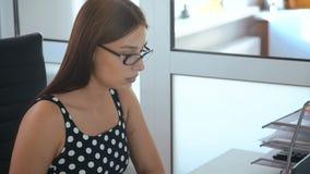 Ελκυστική επιχειρησιακή γυναίκα που εργάζεται με τον υπολογιστή στην αρχή φιλμ μικρού μήκους
