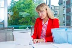 Ελκυστική επιχειρησιακή γυναίκα στην αρχή με το lap-top Στοκ Εικόνες