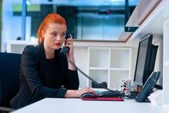 Ελκυστική επιχειρησιακή γυναίκα στο θαλαμίσκο γραφείων στο τηλέφωνο Στοκ εικόνα με δικαίωμα ελεύθερης χρήσης