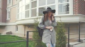 Ελκυστική επιχειρησιακή γυναίκα στο μαύρο καπέλο και γυαλιά που μιλούν σε ένα τηλέφωνο φιλμ μικρού μήκους