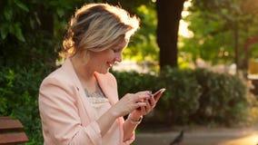 Ελκυστική λευκή γυναίκα ξανθή χρησιμοποιώντας ένα smartphone στο πάρκο στην ηλιόλουστη ημέρα φιλμ μικρού μήκους