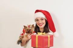 Ελκυστική ευτυχής γυναίκα στο καπέλο Santa με το τεριέ και το παρόν παιχνιδιών Στοκ φωτογραφία με δικαίωμα ελεύθερης χρήσης