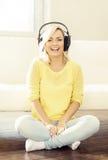 Ελκυστική ευτυχής μουσική ακούσματος κοριτσιών στο σπίτι Στοκ Εικόνα