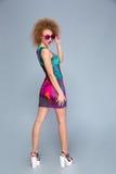 Ελκυστική εύθυμη θηλυκή τοποθέτηση στο ζωηρόχρωμο φόρεμα στοκ εικόνες με δικαίωμα ελεύθερης χρήσης