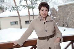 Ελκυστική ηλικιωμένη τοποθέτηση γυναικών στο υπαίθριο πεζούλι το χειμώνα Στοκ φωτογραφία με δικαίωμα ελεύθερης χρήσης