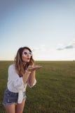 Ελκυστική και όμορφη γυναίκα που φυσά από τα χέρια της που φορούν το προκλητικό τζιν απότομα στοκ φωτογραφία