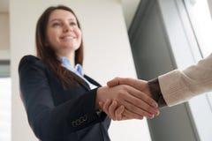 Ελκυστική καλωσορίζοντας επιχειρηματίας που τινάζει το αρσενικό χέρι και το χαμόγελο στοκ εικόνες