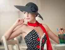 Ελκυστική κυρία με το μαύρο καπέλο και κόκκινη συνεδρίαση μαντίλι στο εστιατόριο Στοκ Εικόνες