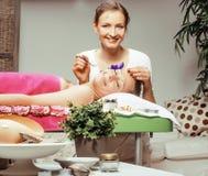 Ελκυστική κυρία φωτογραφιών που παίρνει την επεξεργασία SPA στο σαλόνι με τον εύθυμο γιατρό που χαμογελά τους καυκάσιους ανθρώπου Στοκ φωτογραφία με δικαίωμα ελεύθερης χρήσης