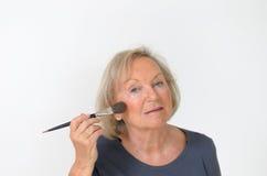 Ελκυστική μέσης ηλικίας γυναίκα που ισχύει makeup Στοκ Εικόνες