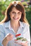 Ελκυστική μέση ηλικίας γυναίκα που τρώει την υγιή σαλάτα στον κήπο Στοκ φωτογραφίες με δικαίωμα ελεύθερης χρήσης