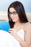 Ελκυστική νέα ανάγνωση γυναικών στο κρεβάτι Στοκ Εικόνες