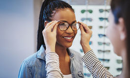 Ελκυστική νέα αφρικανική γυναίκα που επιλέγει τα γυαλιά στοκ εικόνα με δικαίωμα ελεύθερης χρήσης