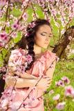 Ελκυστική νέα γυναίκα με τα άνθη στην τρίχα στοκ εικόνα