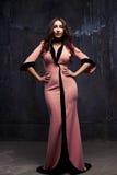 Ελκυστική νέα γυναίκα να εξισώσει το ρόδινο φόρεμα με τα χέρια στα ισχία Στοκ Εικόνες