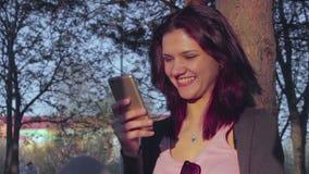 Ελκυστική νέα γυναίκα που δακτυλογραφεί ένα μήνυμα στο τηλέφωνό της φιλμ μικρού μήκους