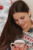 Ελκυστική νέα γυναίκα που απολαμβάνει το ζεστό ποτό στην πλάτη χριστουγεννιάτικων δέντρων Στοκ φωτογραφίες με δικαίωμα ελεύθερης χρήσης
