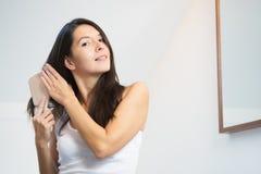 Ελκυστική νέα γυναίκα που βουρτσίζει την μακρυμάλλη Στοκ Φωτογραφίες