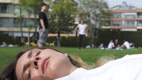 Ελκυστική νέα γυναίκα που βρίσκεται στη χλόη - τα παιδιά έχουν το υπόβαθρο διασκέδασης στο πάρκο απόθεμα βίντεο