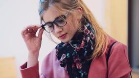 Ελκυστική νέα γυναίκα που διαβάζει το βιβλίο τσεπών στην καφετέρια, έπειτα που διορθώνει σχετικά με τα γυαλιά της Ρομαντικός μοντ απόθεμα βίντεο