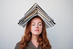 Ελκυστική νέα γυναίκα που ισορροπεί ένα βιβλίο σε την επικεφαλής άσπρο υπόβαθρο Στοκ φωτογραφίες με δικαίωμα ελεύθερης χρήσης