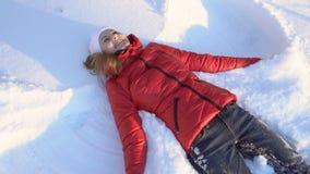 Ελκυστική νέα γυναίκα που κάνει τον άγγελο χιονιού σε ένα χειμερινό πάρκο, που έχει την ανόητη διασκέδαση, χαμόγελο κίνηση αργή απόθεμα βίντεο