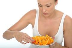 Ελκυστική νέα γυναίκα που κρατά ένα πιάτο των κομμένων πορτοκαλιών Στοκ φωτογραφίες με δικαίωμα ελεύθερης χρήσης