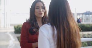 Ελκυστική νέα γυναίκα που μιλά σε μια φίλη φιλμ μικρού μήκους