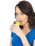 Ελκυστική νέα γυναίκα που πίνει το χυμό της Apple Στοκ εικόνα με δικαίωμα ελεύθερης χρήσης