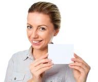 Ελκυστική νέα γυναίκα που παρουσιάζει κενό κενό σημάδι καρτών εγγράφου με το διάστημα αντιγράφων για το κείμενο Στοκ Εικόνες
