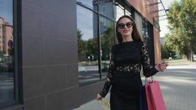 Ελκυστική νέα γυναίκα που περπατά κεντρικός με τις τσάντες αγορών που απολαμβάνουν την ημέρα της απόθεμα βίντεο