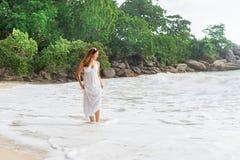 Ελκυστική, νέα γυναίκα που περπατά στην ακτή και που σηκώνει το φόρεμα στοκ φωτογραφίες