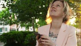 Ελκυστική νέα γυναίκα που περπατά στο πάρκο και τις χρήσεις ένα smartphone φιλμ μικρού μήκους