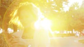 Ελκυστική νέα γυναίκα που περπατά στο πάρκο και τις χρήσεις ένα smartphone απόθεμα βίντεο